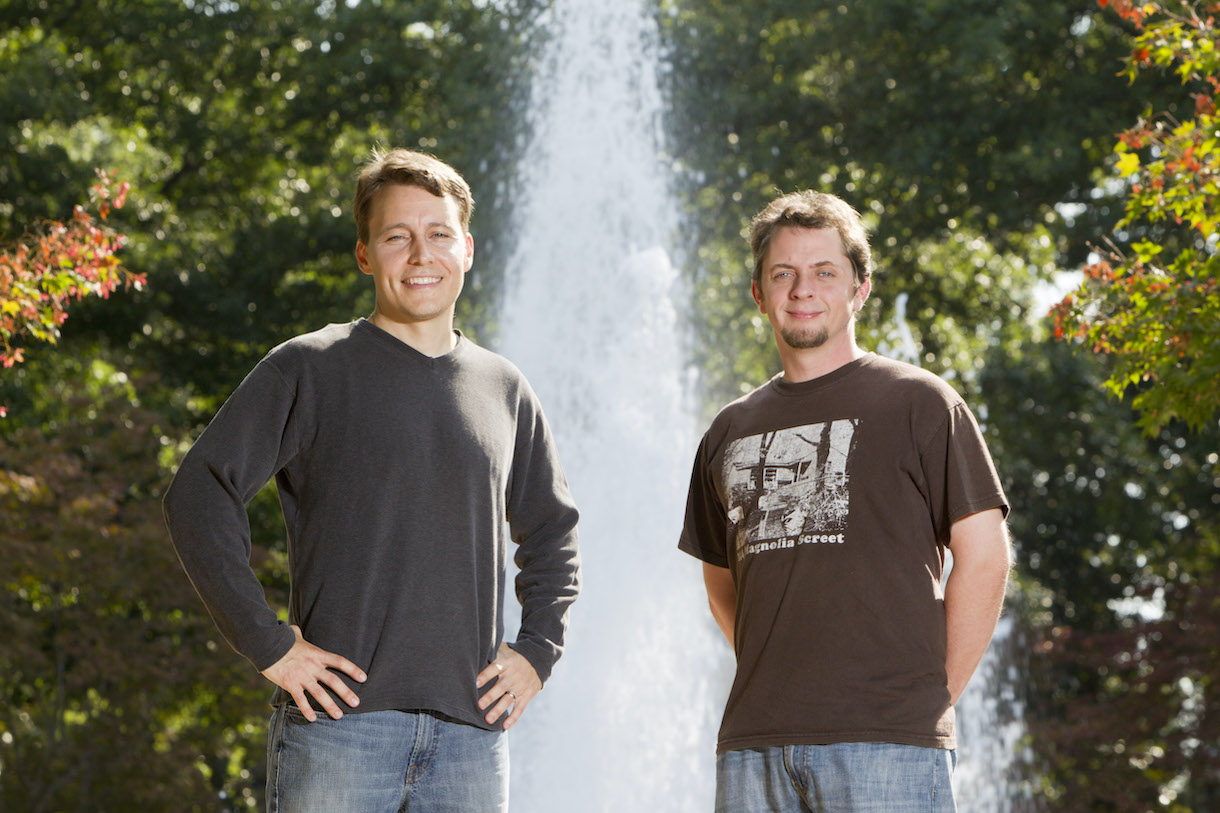 two men pose in front of fountain