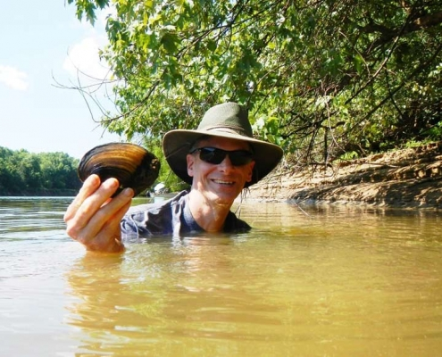 Frank Henning (PhD '10) in holding up a river mussel.