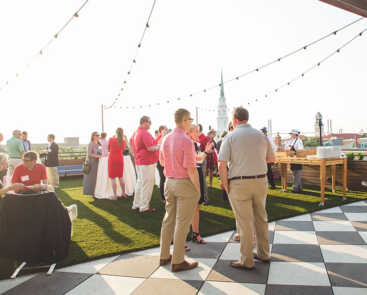 UGA alumni and friends converse on Perry Lane Hotel's rooftop.