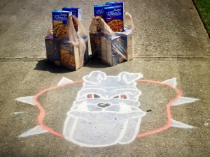 Donated food and a chalk image of Hairy Dawg.